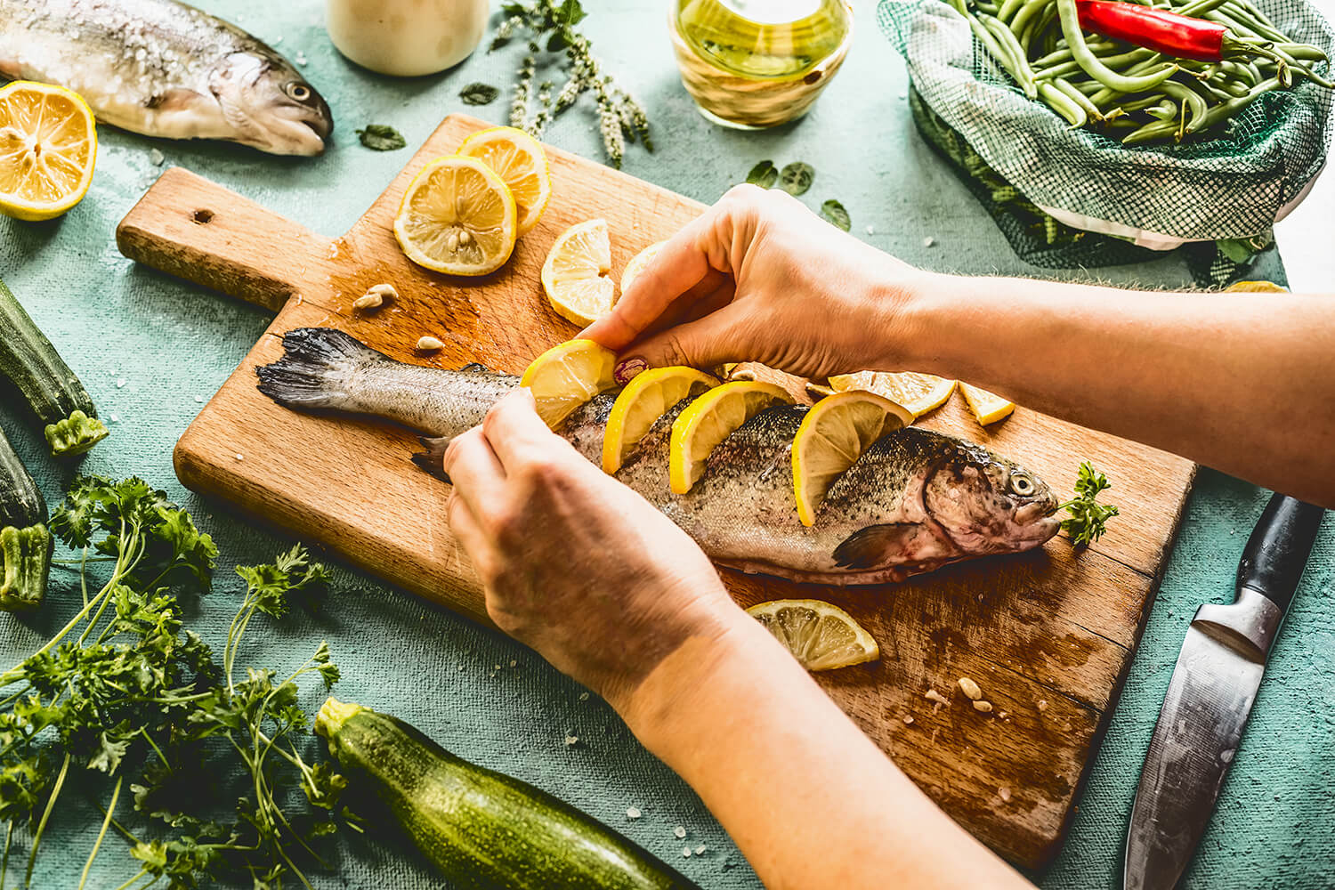 A whole fish laid down on a rustic wooden cutting board garnished with sliced lemons.