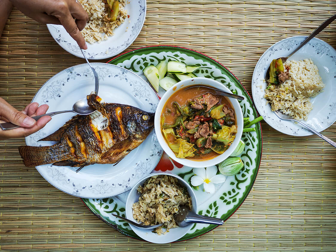 A roasted whole fish resting on a white plate accompanied by curry, rice and vegetables.