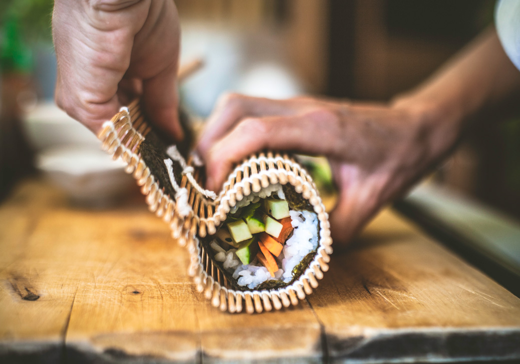 Fresh sushi being wrapped together using a bamboo rolling mat.