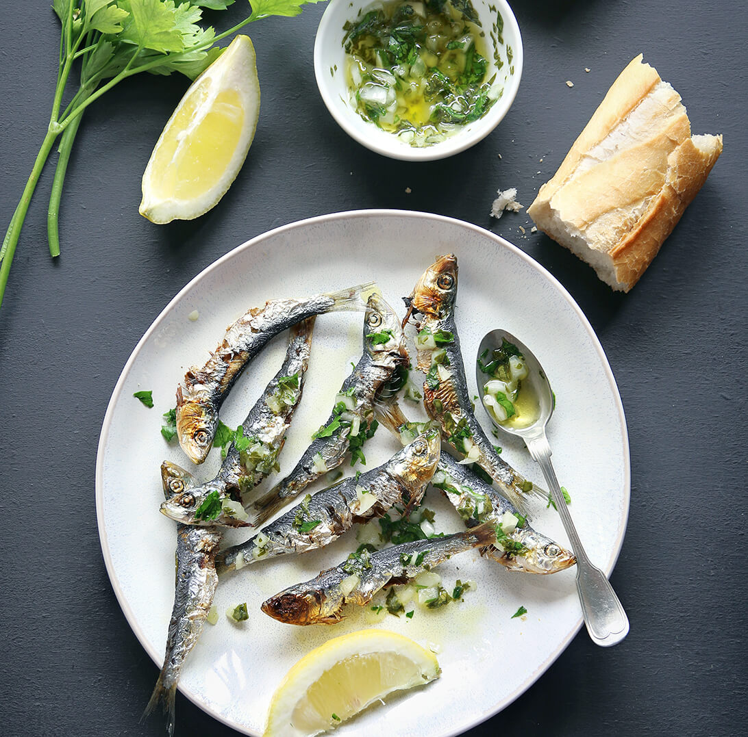 Roasted sardines on a clean white plate garnished with sliced lemons and cilantro.