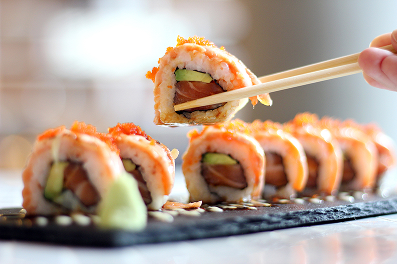 Wooden chopsticks lifting up a single, delicate roll of sushi.