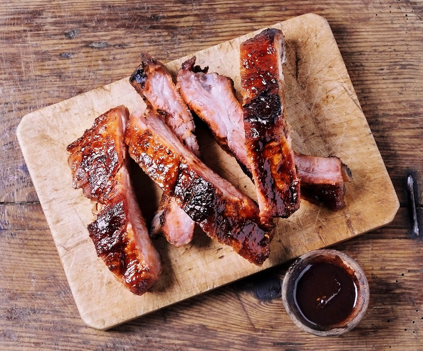 A sliced rack of barbeque ribs resting on a wooden cutting board.
