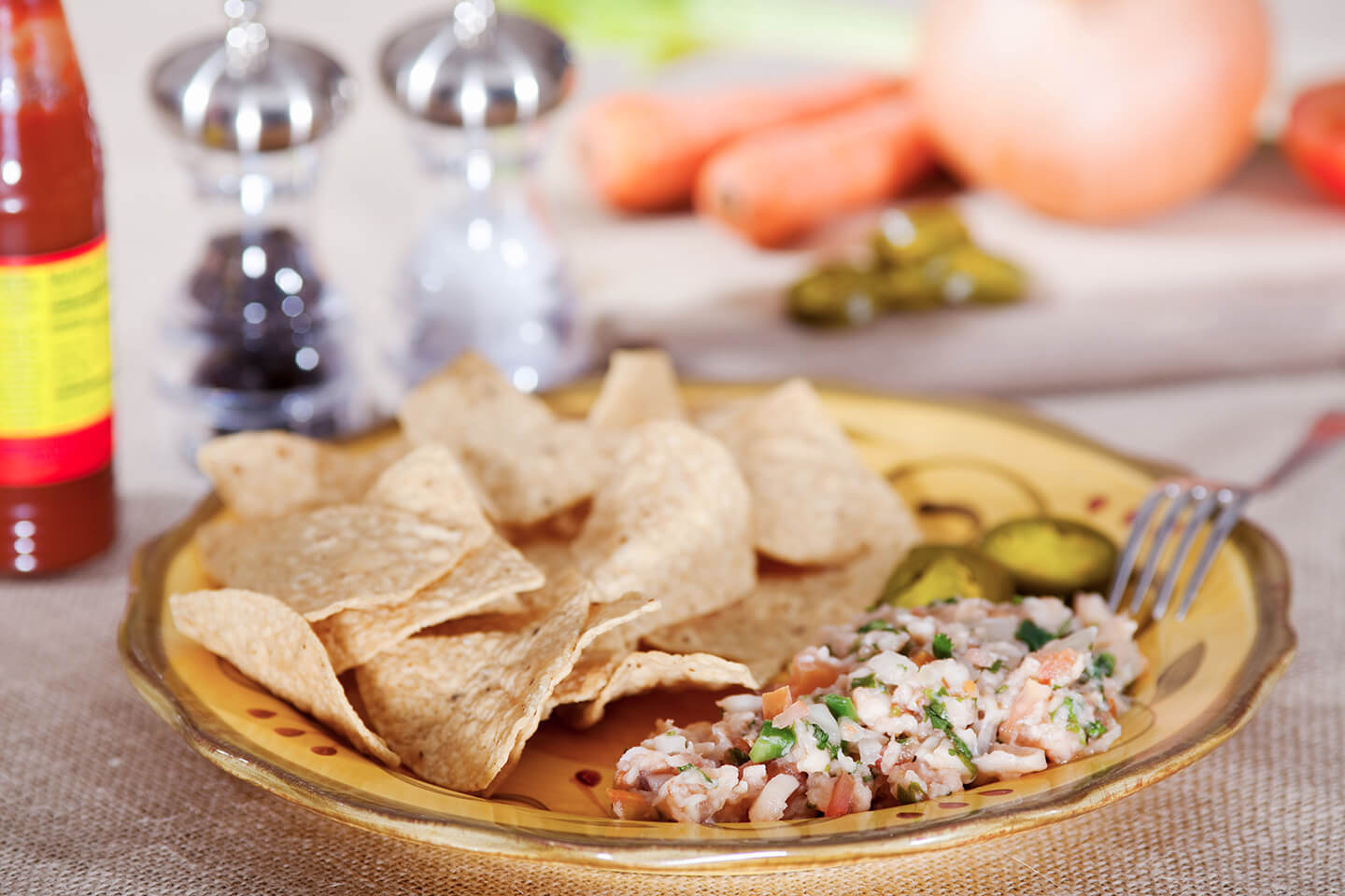 A plate filled with crisp tortilla chips and freshly made ceviche.