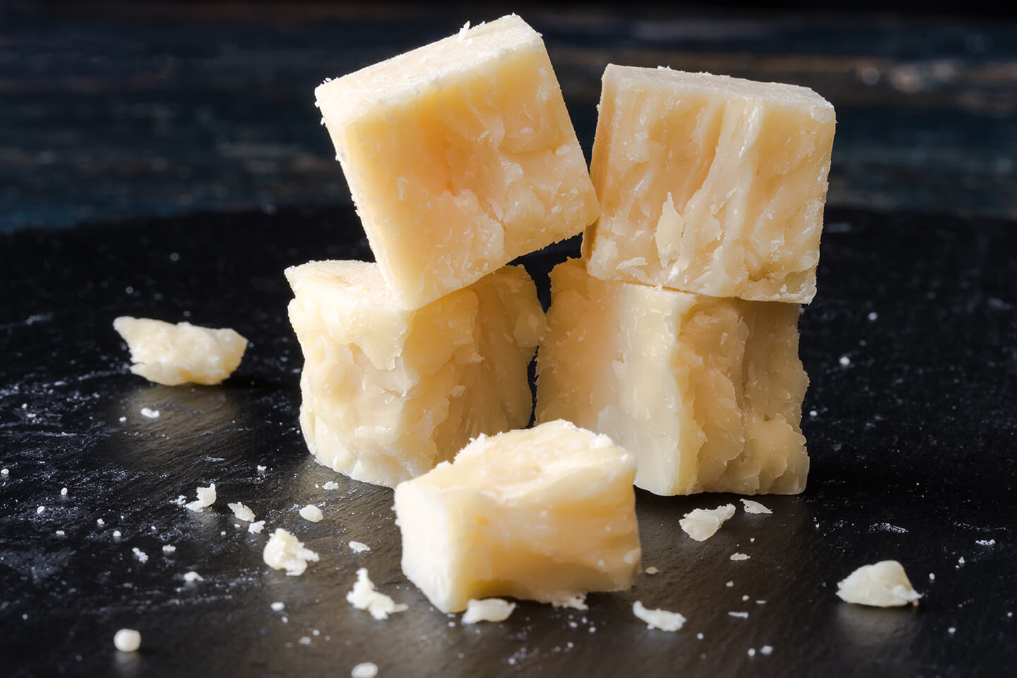 Crumbling cheese cut up into delicate cubes on a dark wooden cutting board.