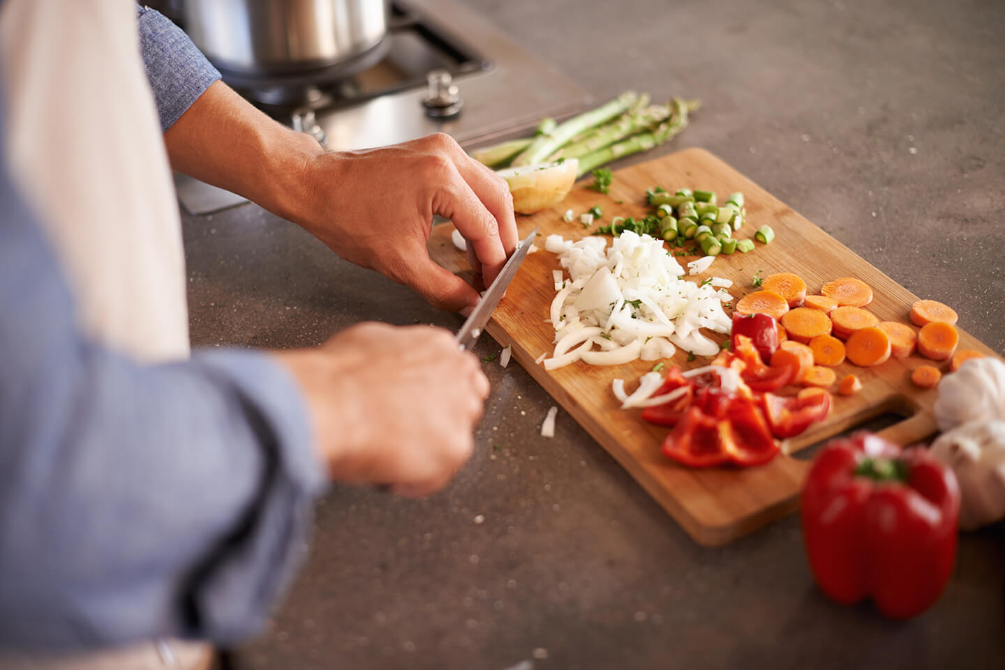 A person dicing white onions on a wooden cutting board along with diced asparagus and tomatoes.