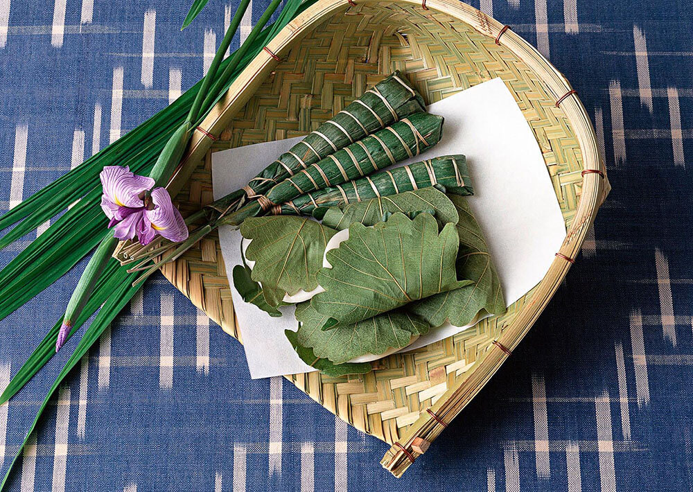 Bundles of bamboo leaves resting in a woven basket.