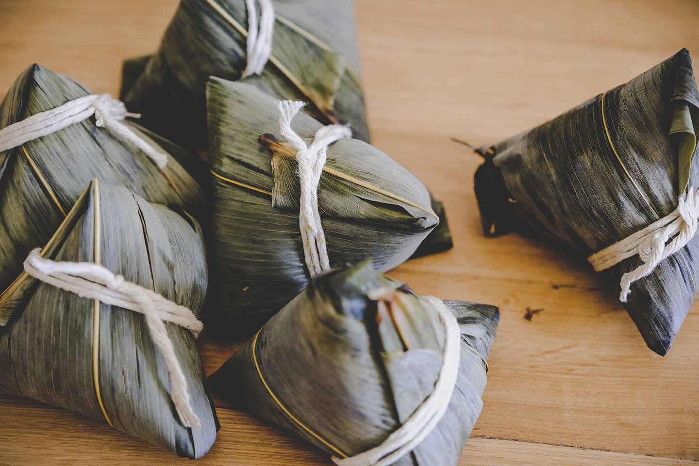 Bundles of food wrapped in bamboo leaves tied shut with twine.