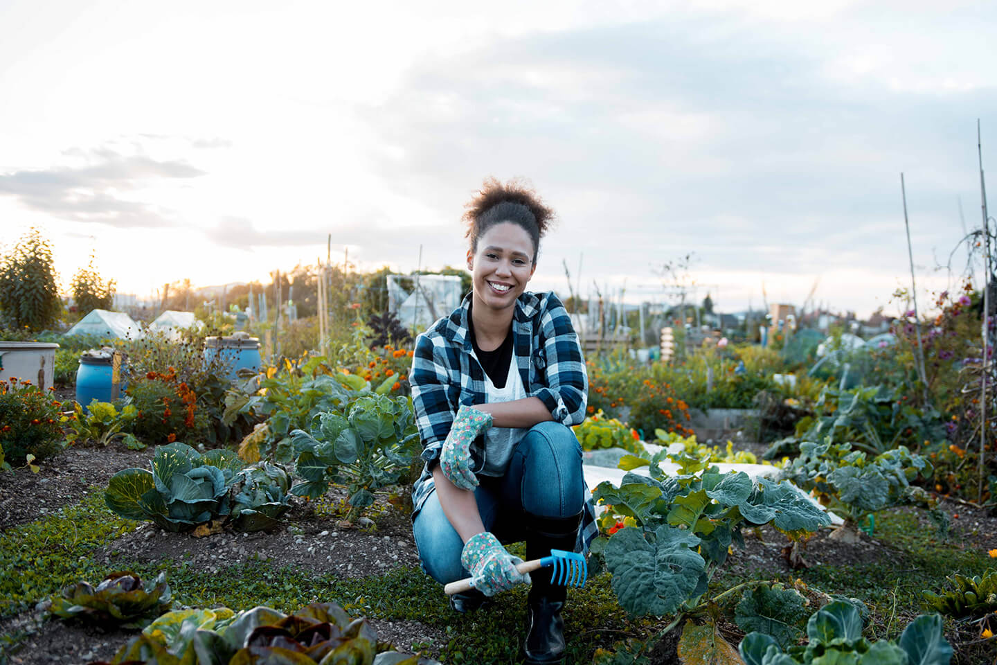 A young woman smiling for the camera in her gardening element.