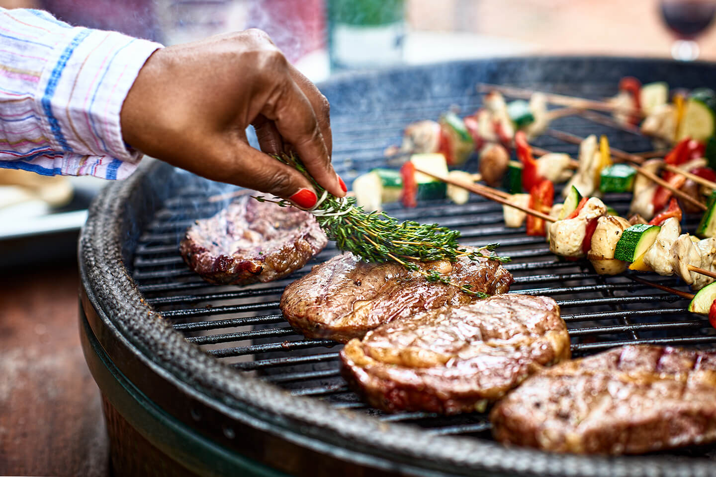 A hand basting grilled steaks in olive oil with a tied bunch of thyme.