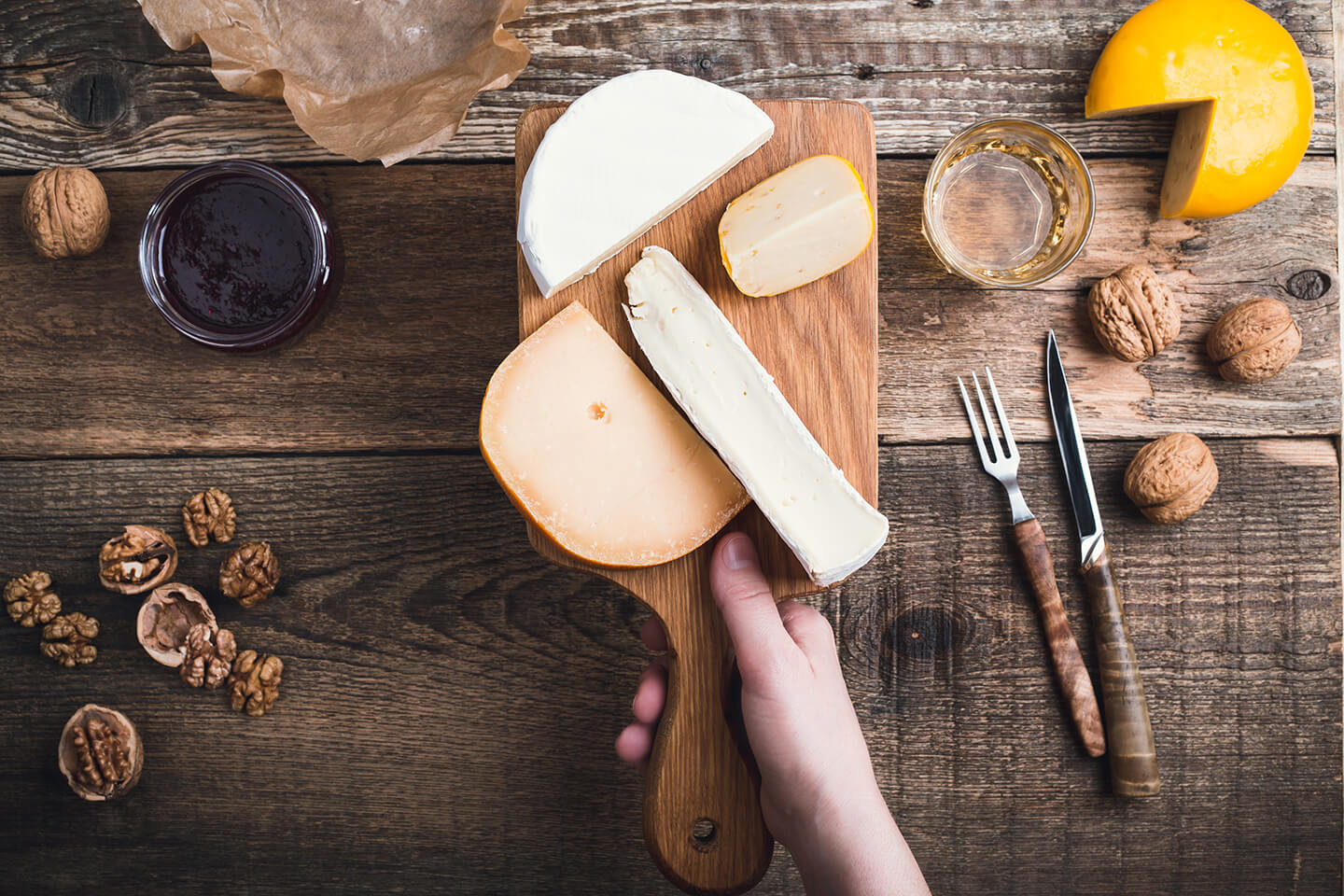 A hand holding up a rustic, wooden cheese board with assorted cheeses.