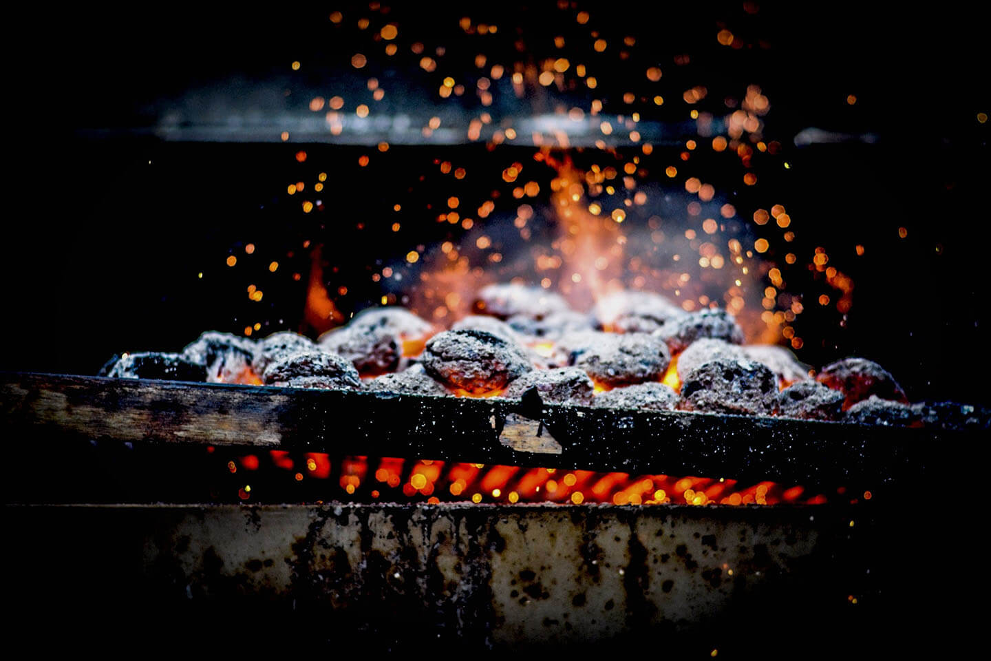 Charcoal burning into bright embers on a grill grate.