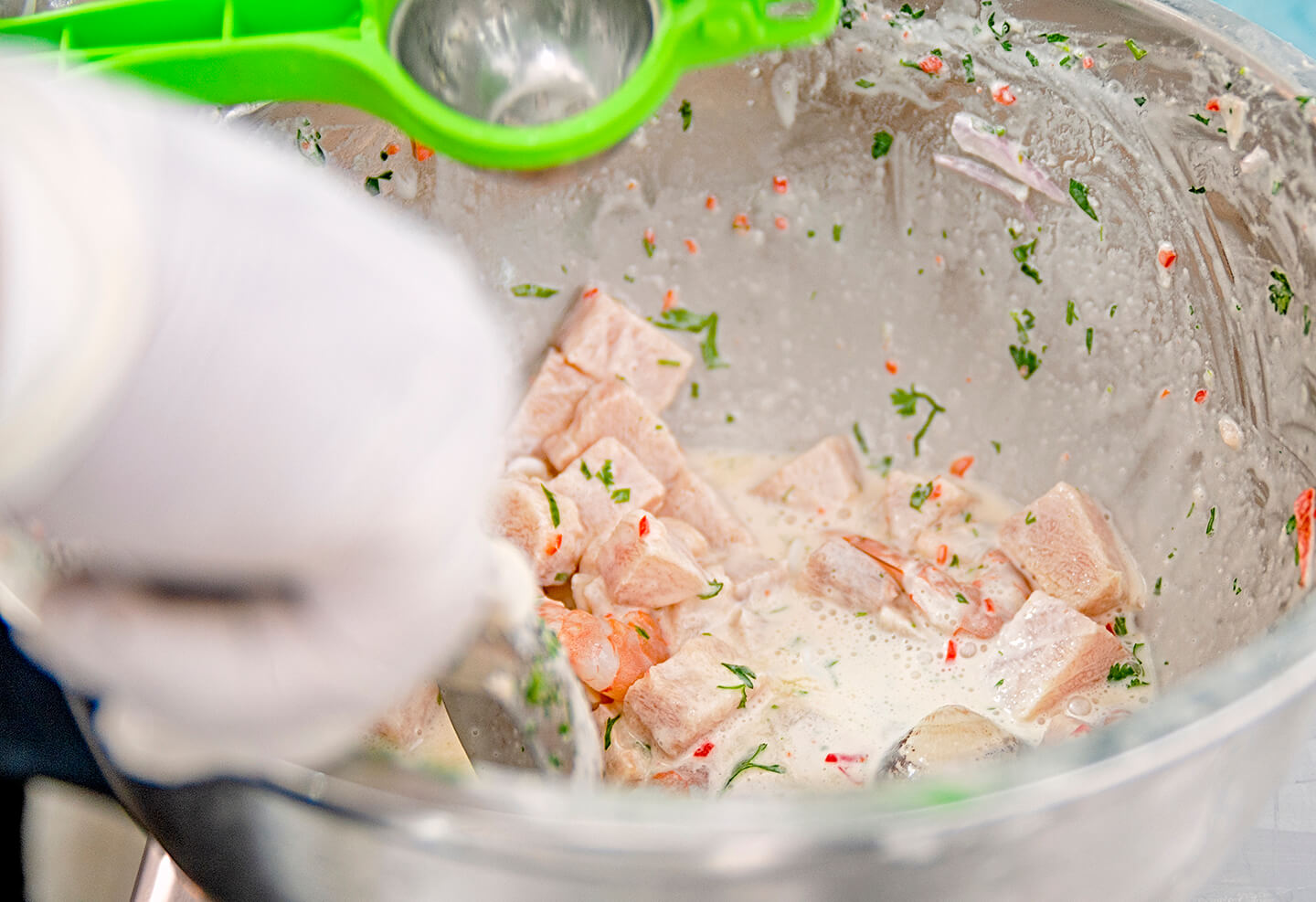 Ceviche being freshly made and seasoned in a large glass bowl.