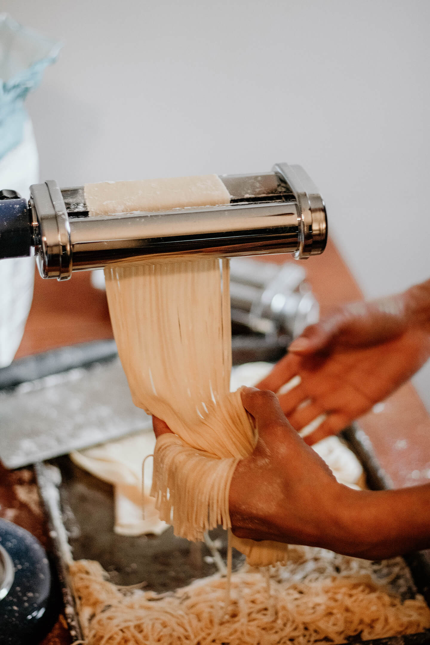 A person making homemade pasta with a KitchenAid® pasta roller attachment.