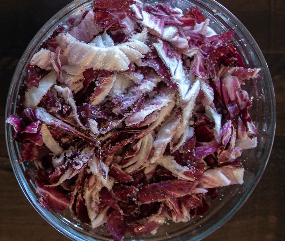 A glass bowl filled with sliced, salted red cabbage.