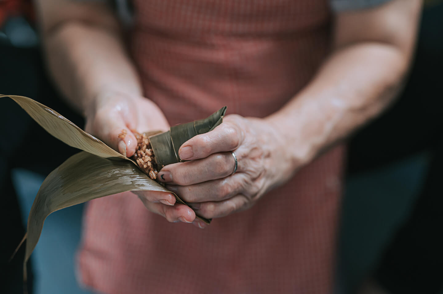 Expert hands gently wrapping rice in bamboo leaves.