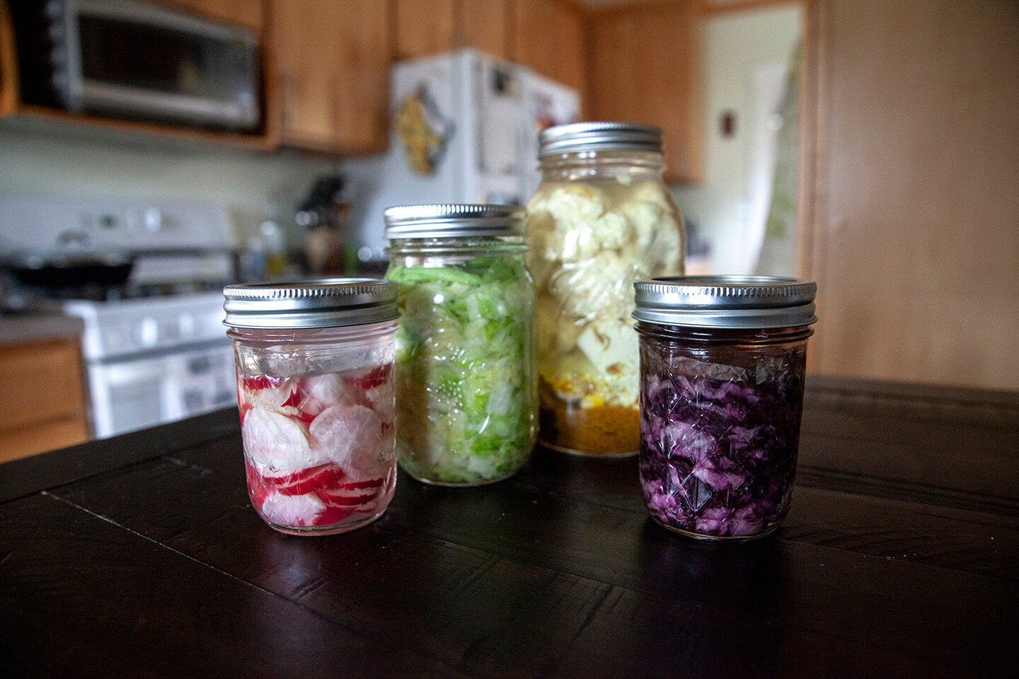 Four sealed, glass jars holding a variety of fermented vegetables.