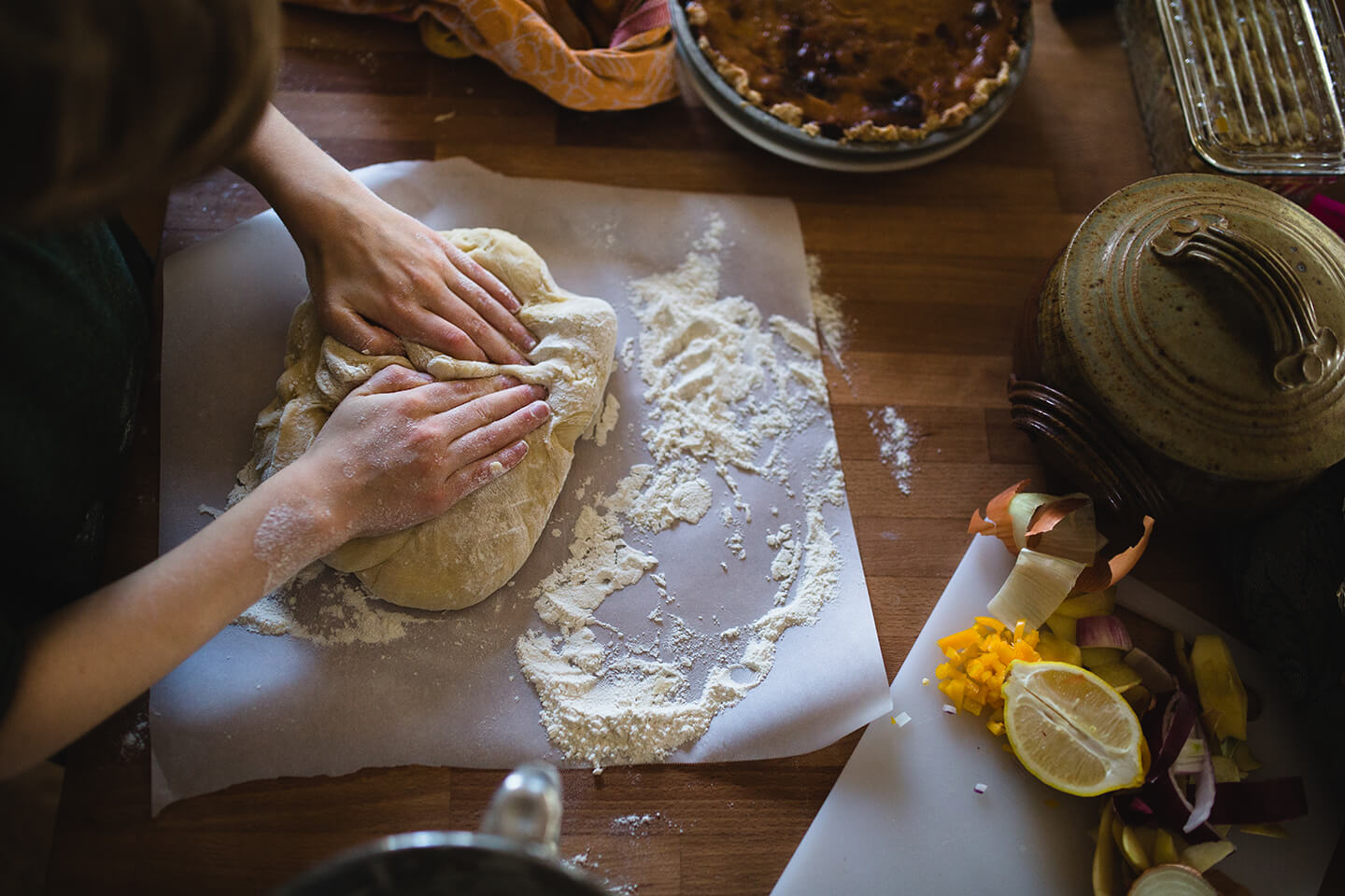 A person gently working dough with flour on parchment paper.