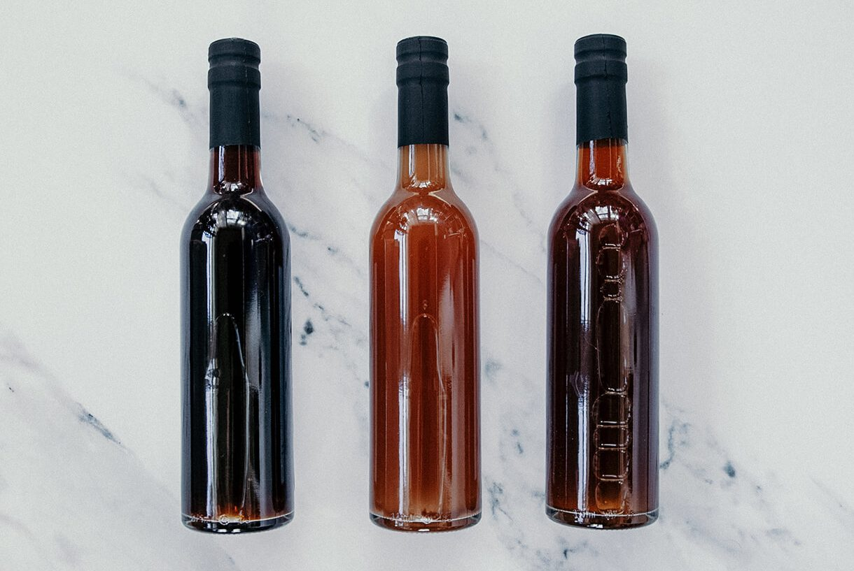Three bottles of varying shades of brown holding vinegar.