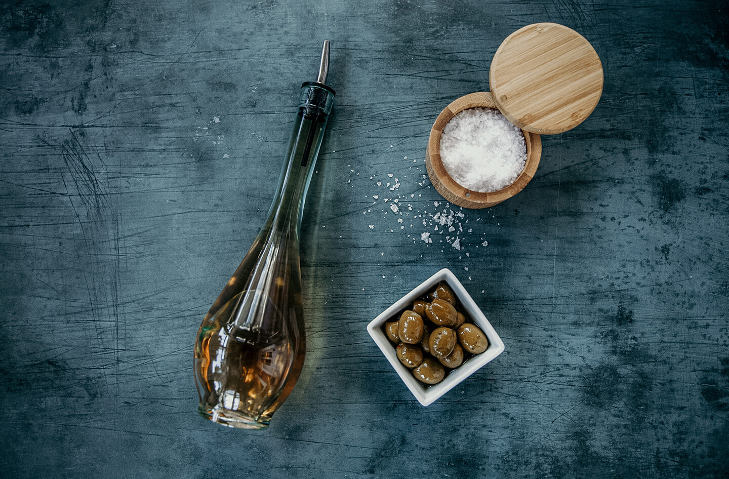 A bottle of vinegar, a dish of olives and a container of kosher salt resting on a table.