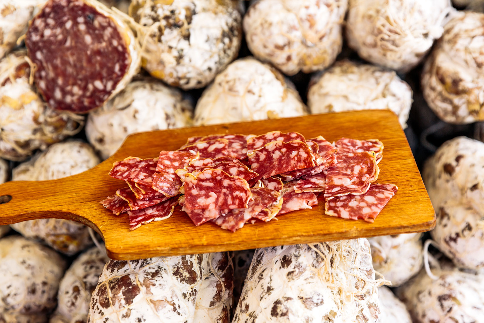 A wooden cutting board holding slices of fine meats.