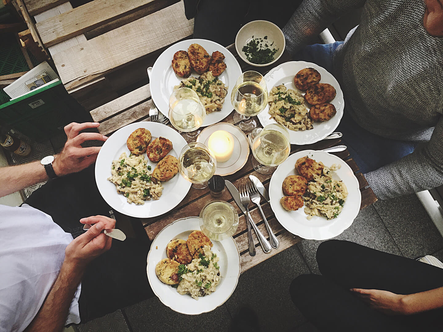 A circle of friends seated arounding a small table filled with food.
