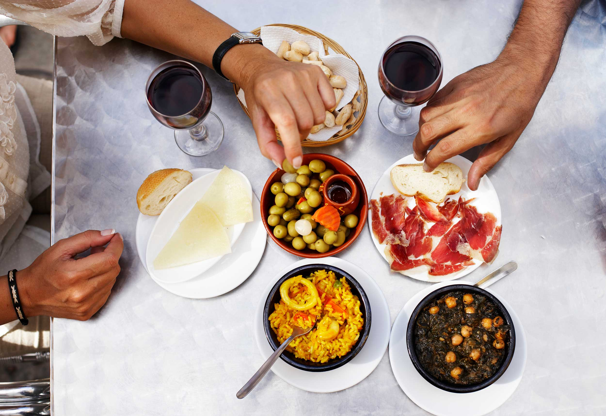 Friends gathered around a table filled with glasses of red wine and fine eats.