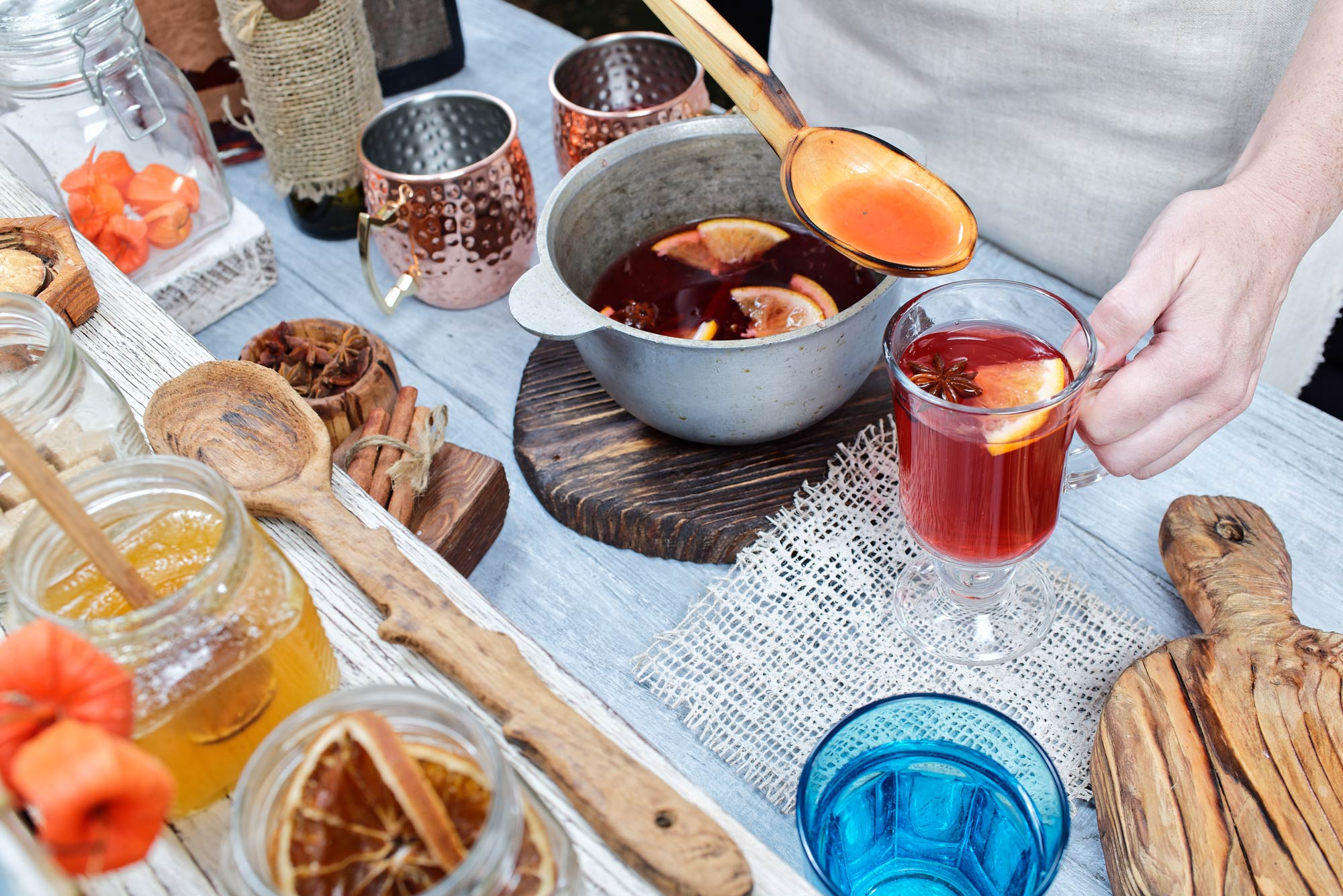 A person serving Austrian gluhwein, mulled red wine with cinnamon, star anise, vanilla and citrus.