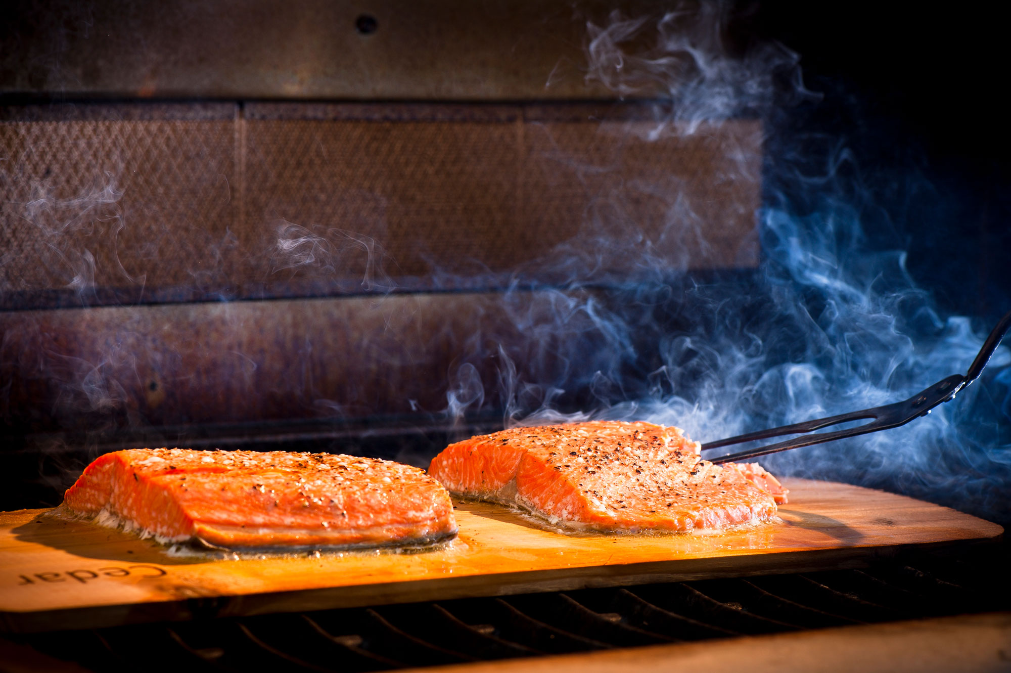 Two salmon fillets cooking on a thin, wooden plank.
