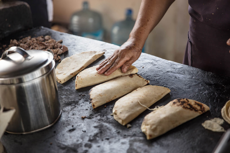 A person tending to folded flour tortillas.
