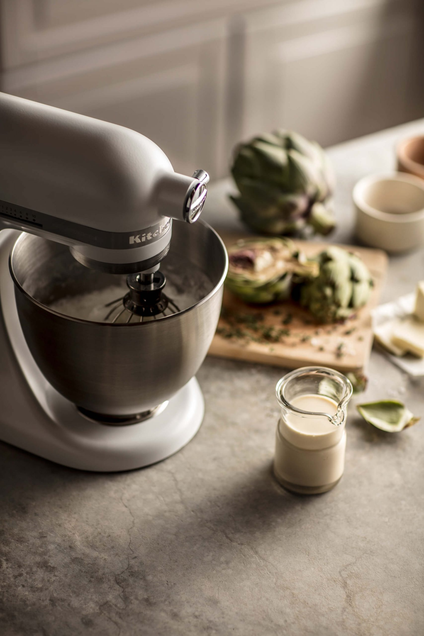 A KitchenAid® Stand Mixer mixing away on a kitchen countertop.