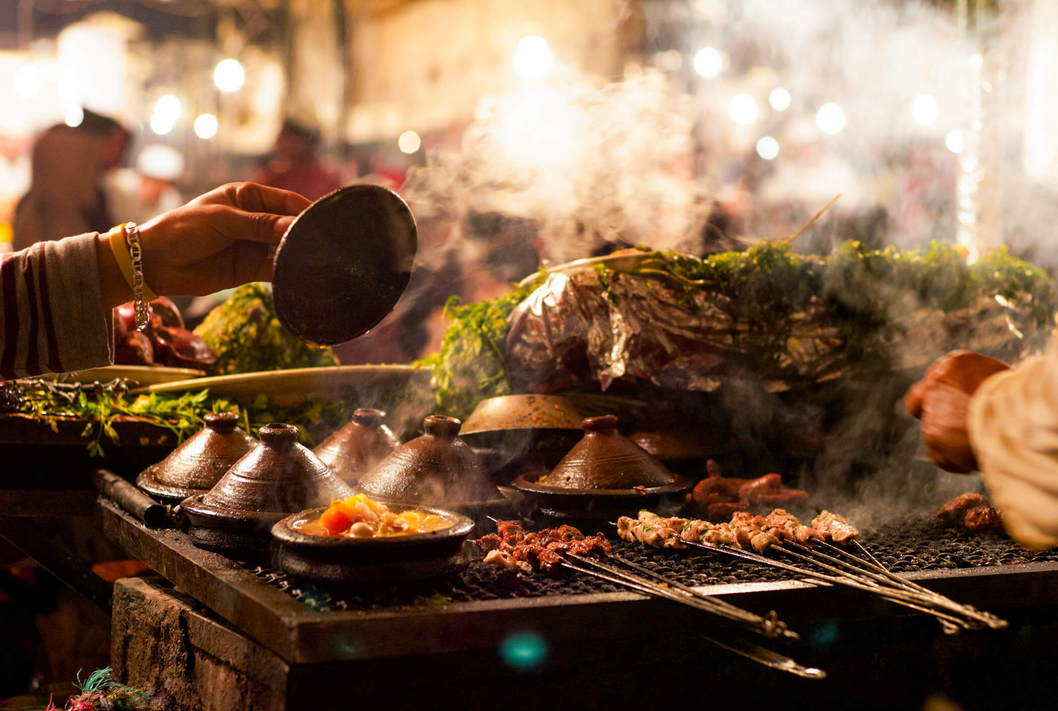 A woman checking her tagine pots as they sit on a large grill with various meats and kebabs.