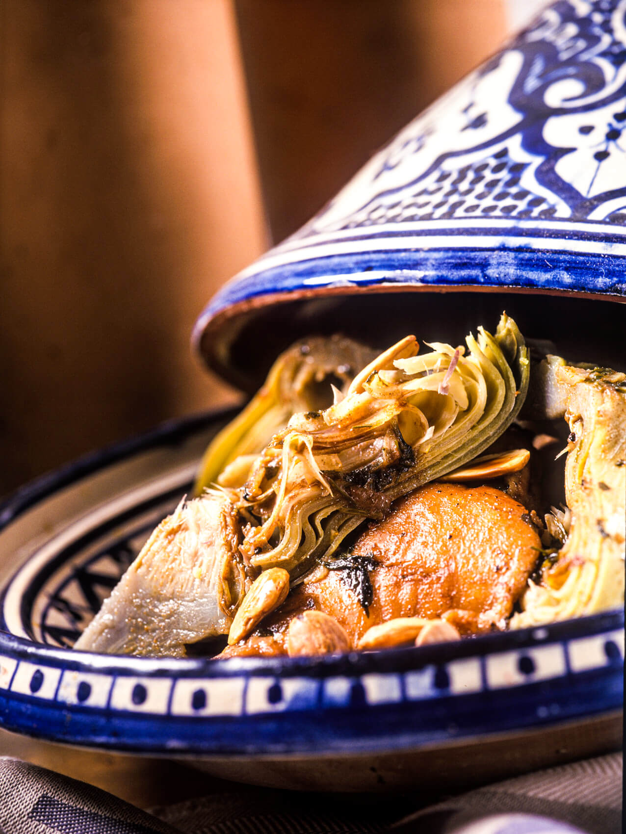 An open tagine filled with shredded artichokes, chicken and other ingredients.