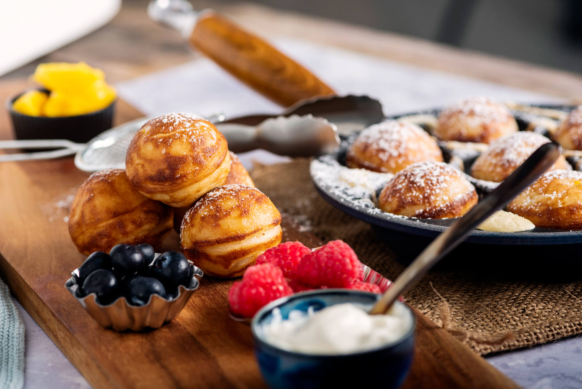 Danish pancake balls topped with powdered sugar and accompanied by a variety of fresh berries.