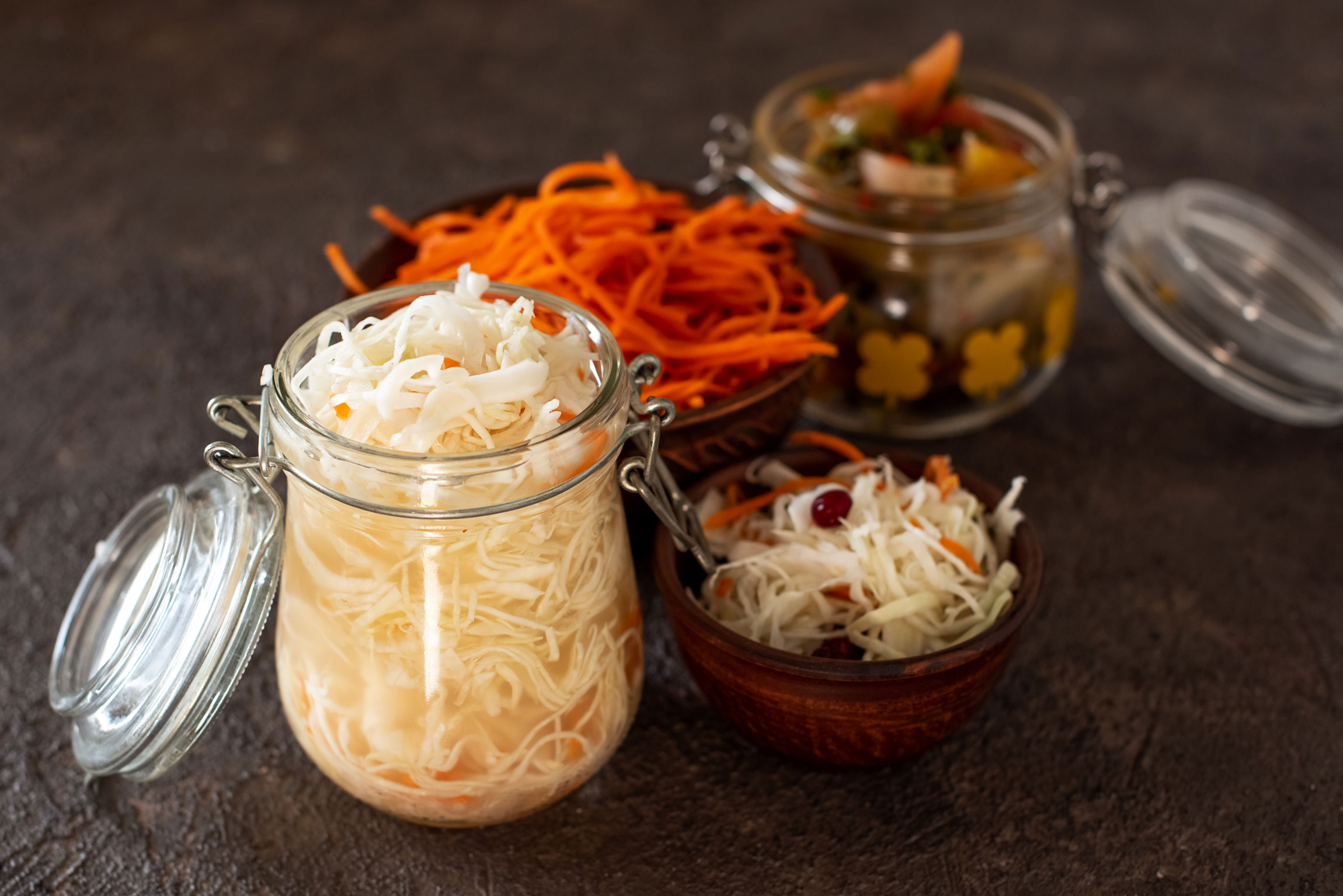 A large, open glass jar filled to the rim with sauerkraut.