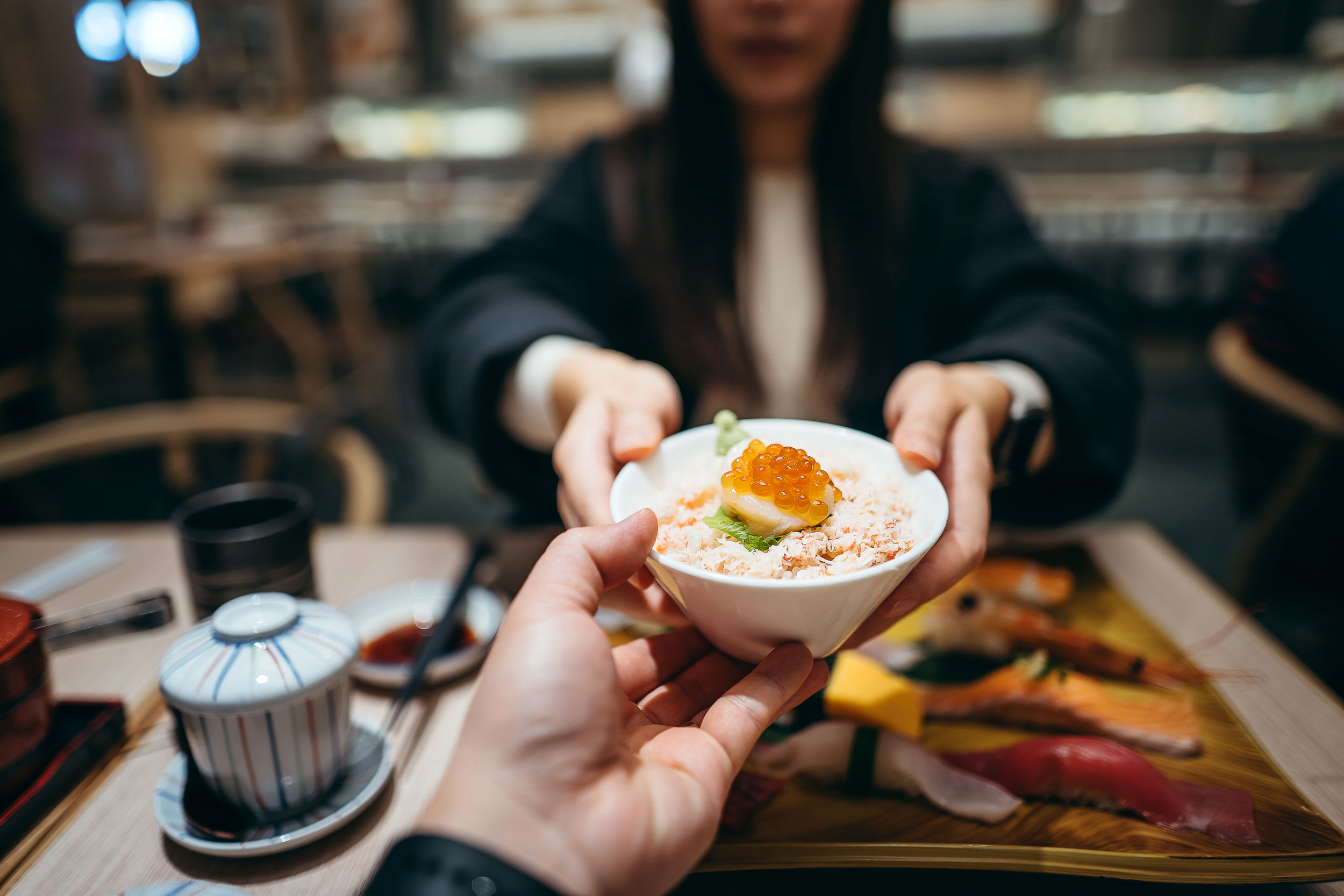 A person handing a small bowl filled with seafood donburi to a young woman.