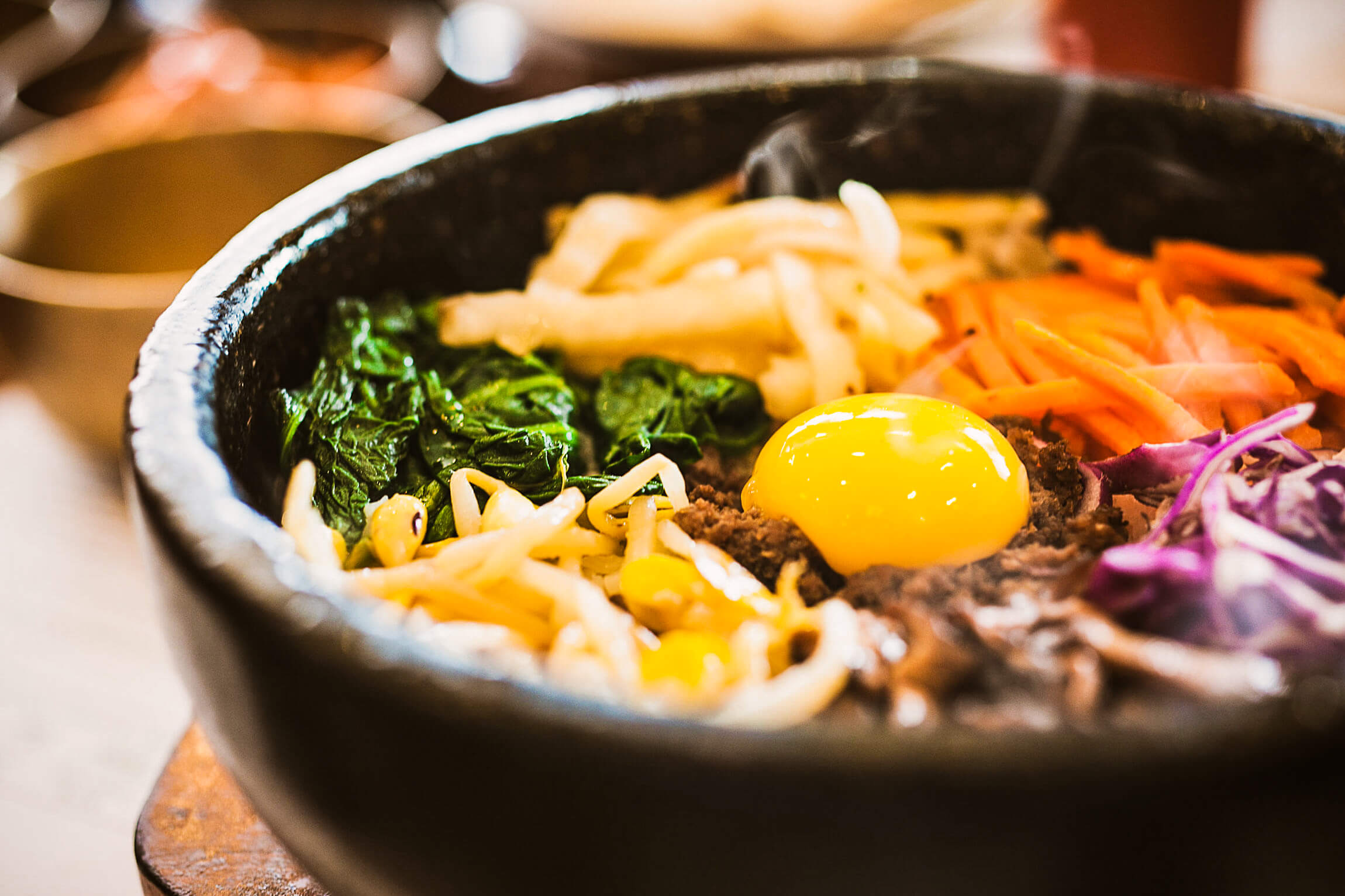 A dolsot bowl filled with bibimbap, a layer of rice topped with meats, veggies and an over-easy egg.