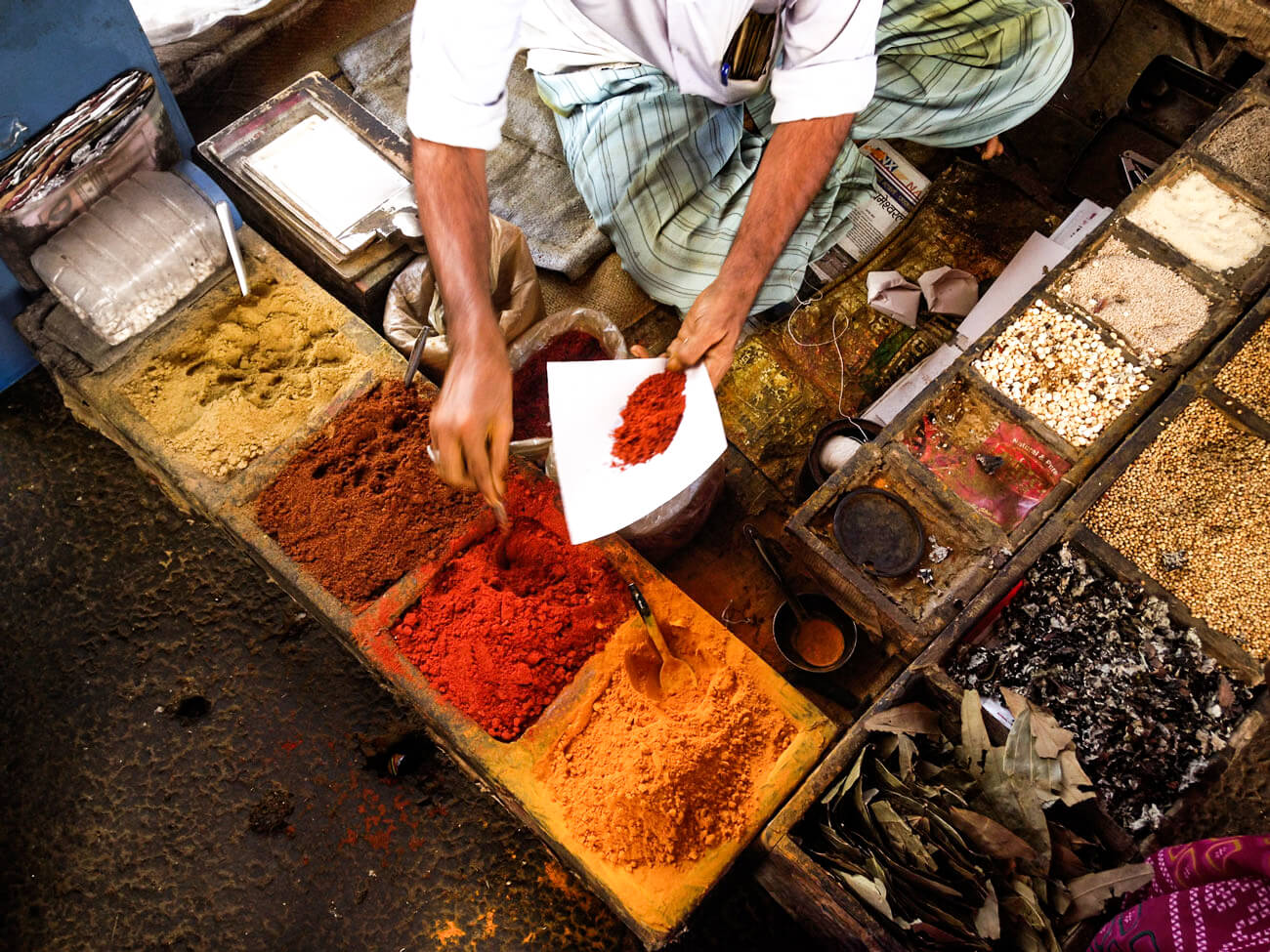 A person collecting a red spice amongst a variety of colorful spices, seasonings and dried herbs.