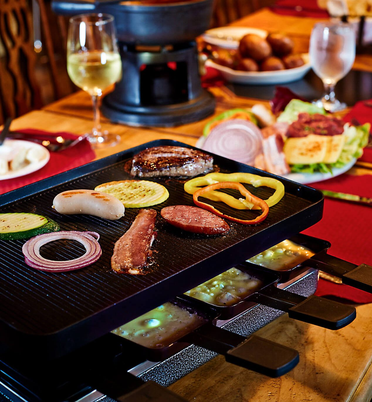 A raclette grill with a griddle on top cooking various meats and vegetables.