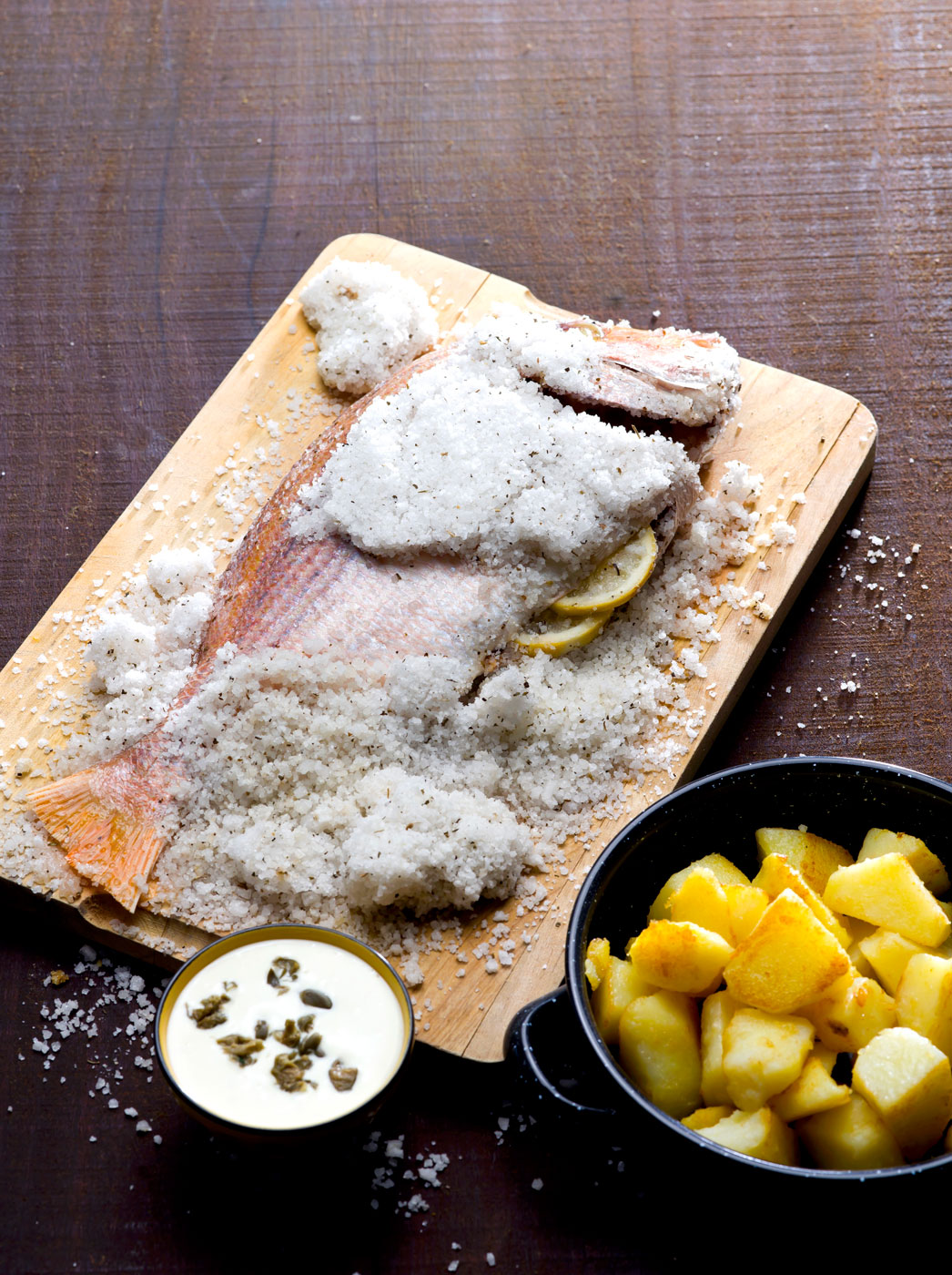 A whole fish in the process of being salt-crusted.