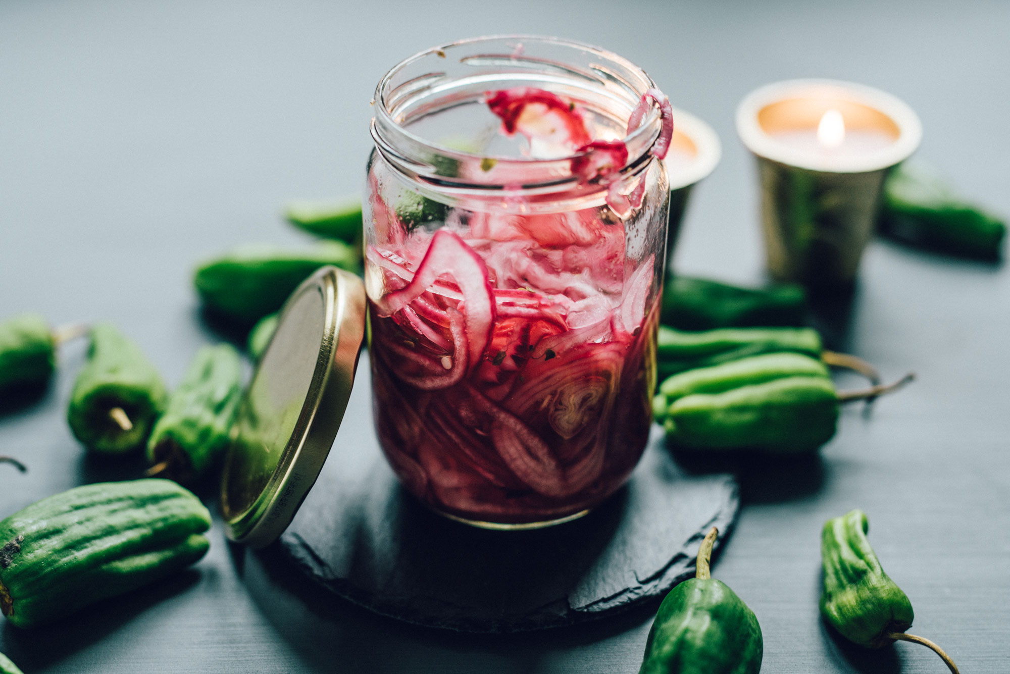A small, open glass jar filled with sliced, pickled red onion.