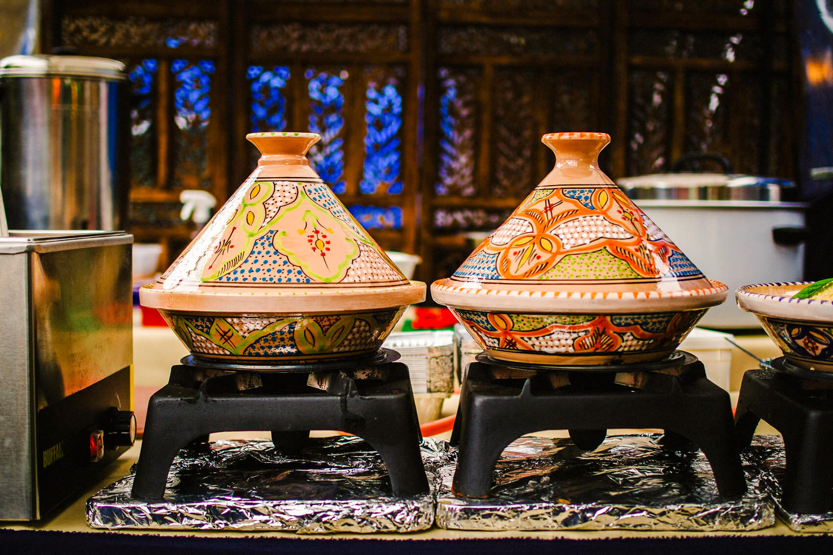 Two colorful, beautifully painted tagine pots set on top of black cooking grates.