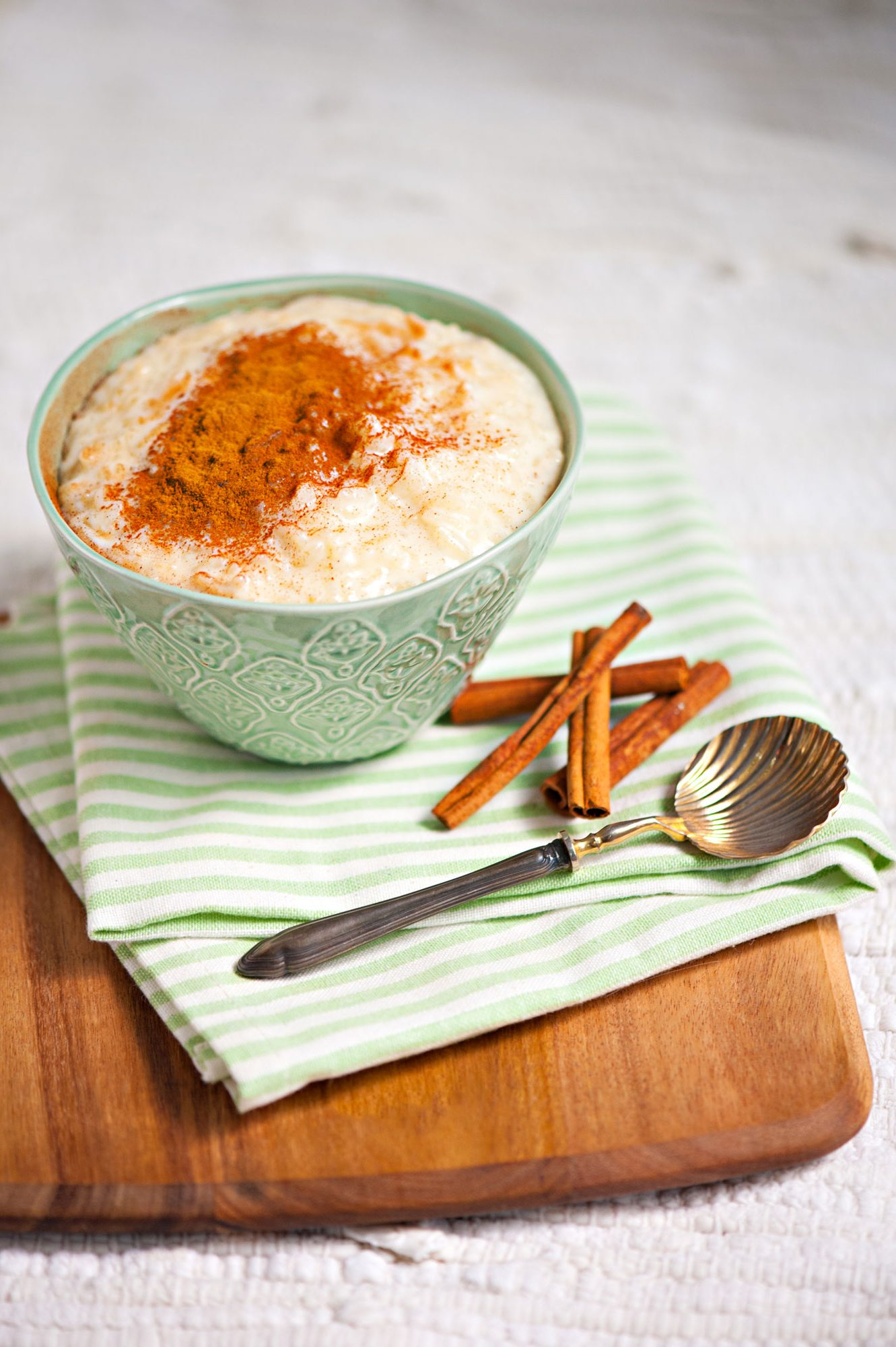 Rice pudding sprinkled with cinnamon in a intricate green bowl.