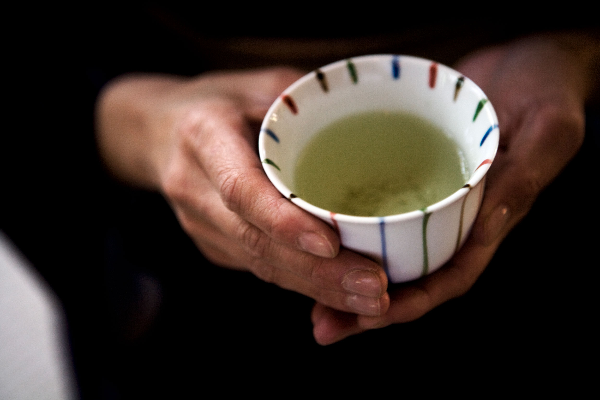 Calm hands holding a small ceramic cup filled with green tea.
