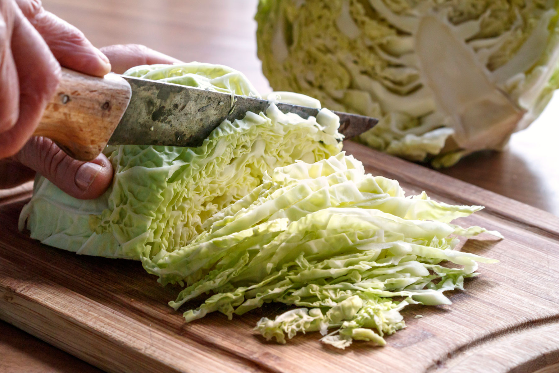 A person thinly chopping a halved cabbage on a wooden cutting board.