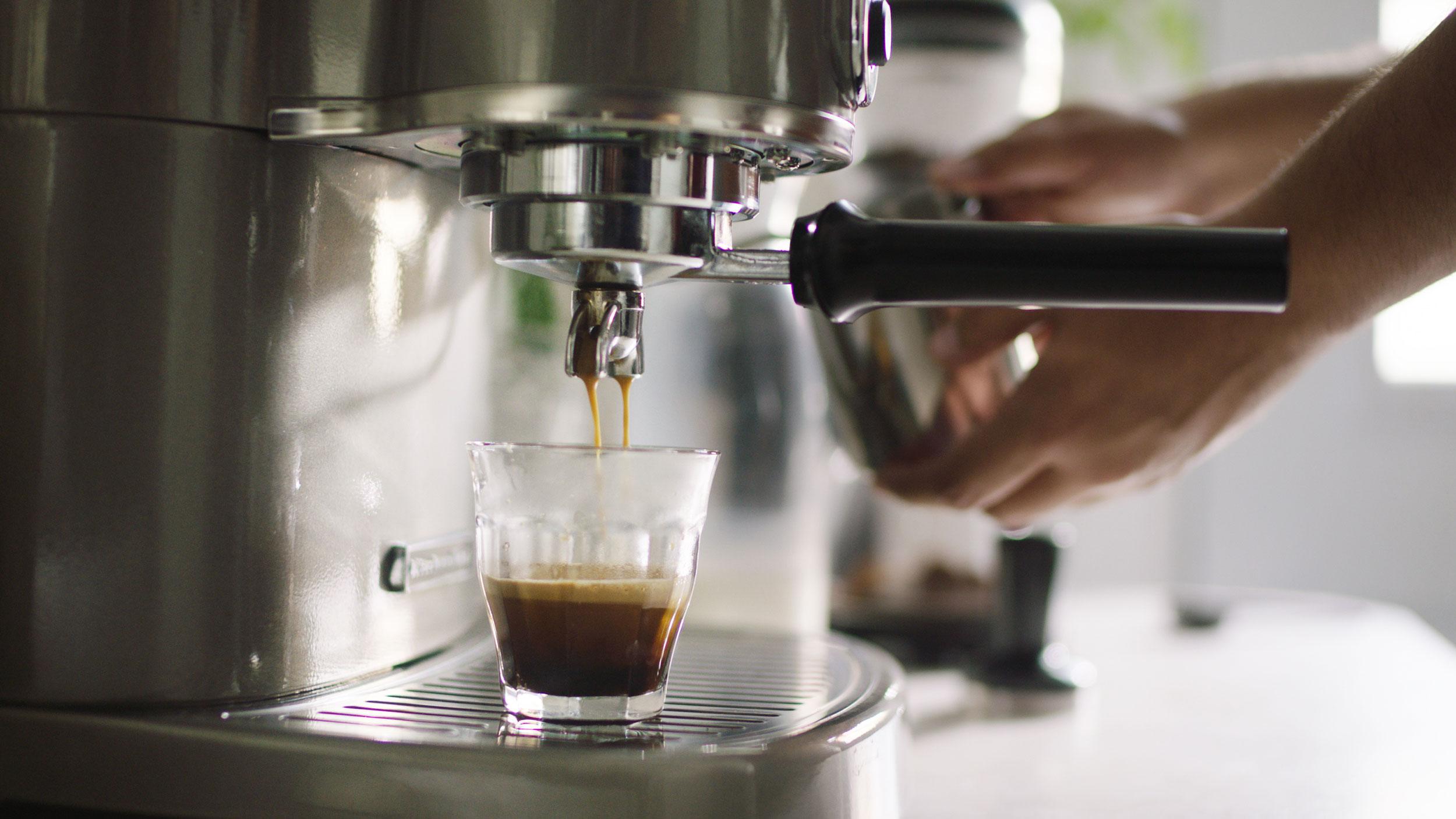 A person making espresso with a KitchenAid® Pro Line® Series Espresso Maker.