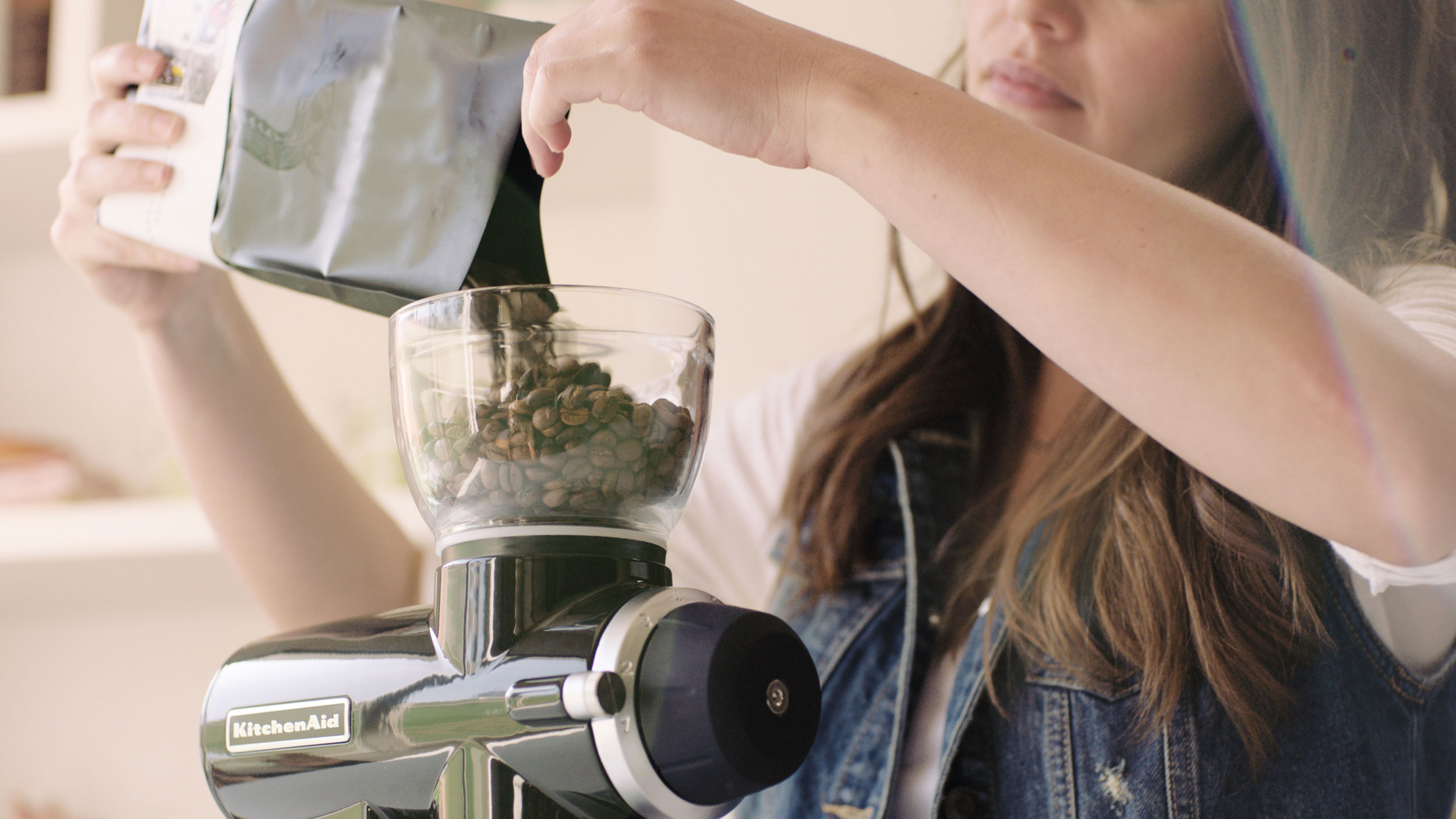 A young woman pouring a small bag of coffee beans into a KitchenAid® Burr Grinder.