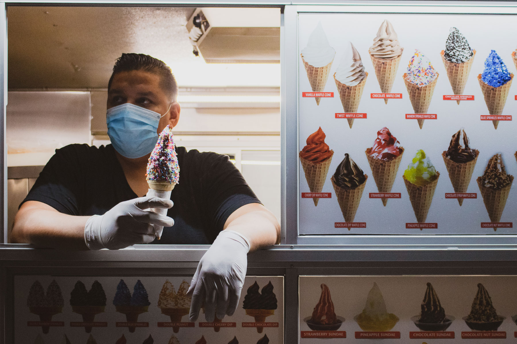 Andy Alvarez inside his ice cream truck holding an ice cream cone loaded with sprinkles.