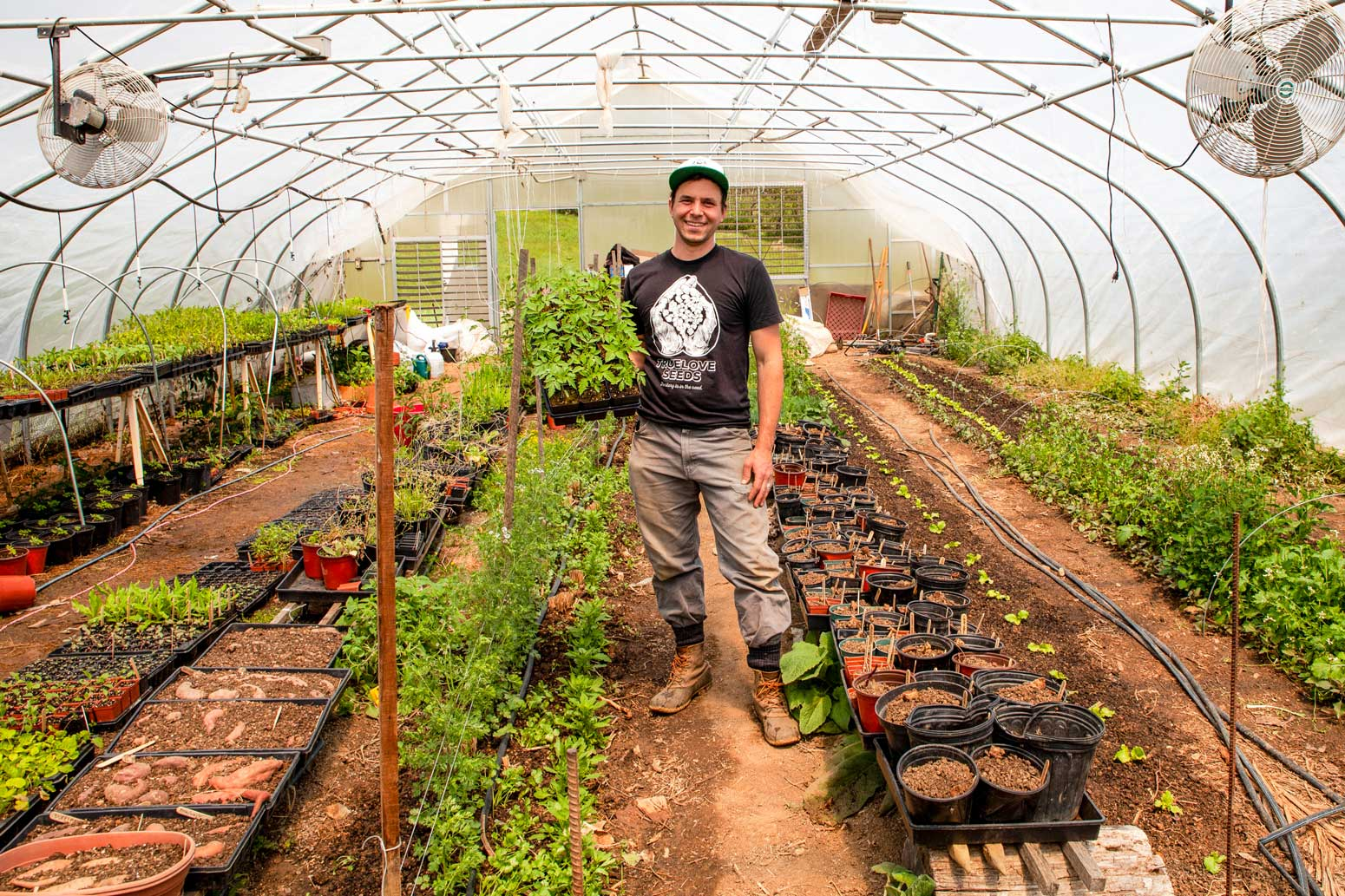 A gardener proudly showing off his nursery plants.