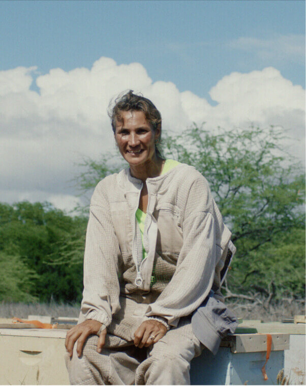 A woman in a beekeeping suit sitting down, smiling for the camera.