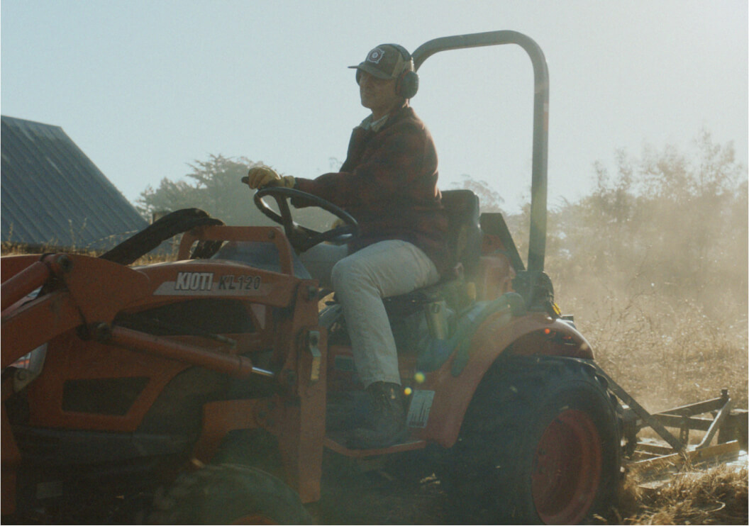 A man driving a small tractor.
